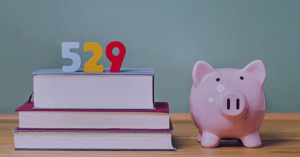 Piggy Bank and 529 block numbers on top of school books representing the 529 Education Savings Plan