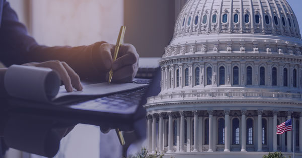 Double exposure of a businessperson signing a check next to the Capitol building where the CARES Act was signed offering the Payroll Tax Credit to help businesses.